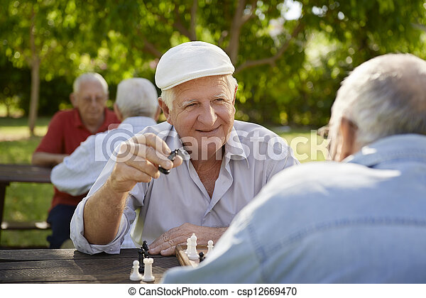 Active retired seniors, two old men playing chess at park - csp12669470