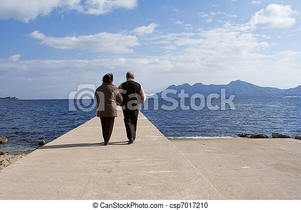 active senior couple walking by the sea on vacation - csp7017210