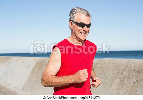 Active senior man jogging on the pier - csp21841279