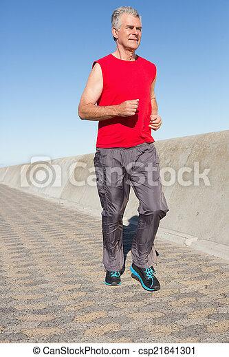 Active senior man jogging on the pier - csp21841301