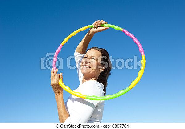 Active senior woman hula hoop exercise - csp10807764