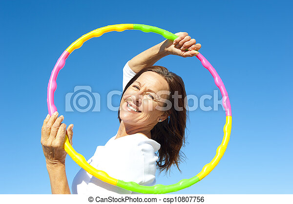 Active senior woman hula hoop exercise - csp10807756