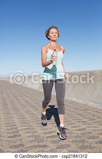Active senior woman jogging on the pier - csp21841312