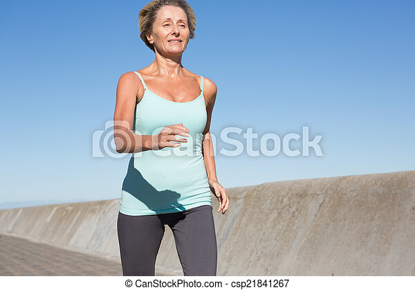 Active senior woman jogging on the pier - csp21841267