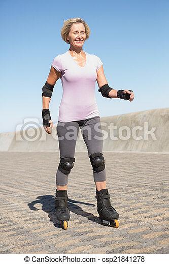 Active senior woman rollerblading on the pier - csp21841278