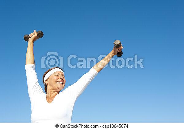 Active senior woman sky background - csp10645074