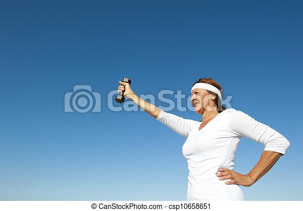 Active senior woman sky background - csp10658651
