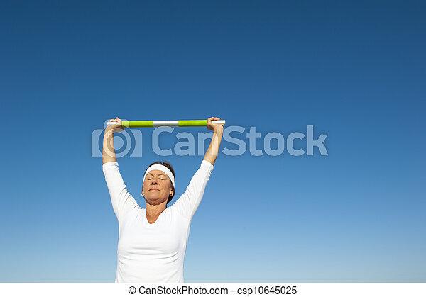 Active senior woman sky background - csp10645025