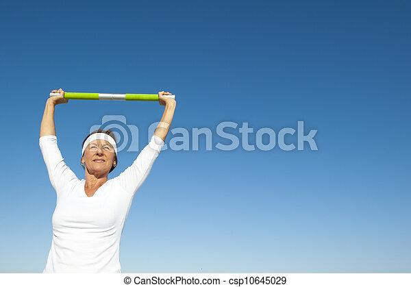 Active senior woman sky background - csp10645029