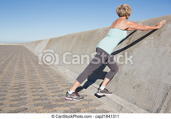 Active senior woman stretching on the pier - csp21841311