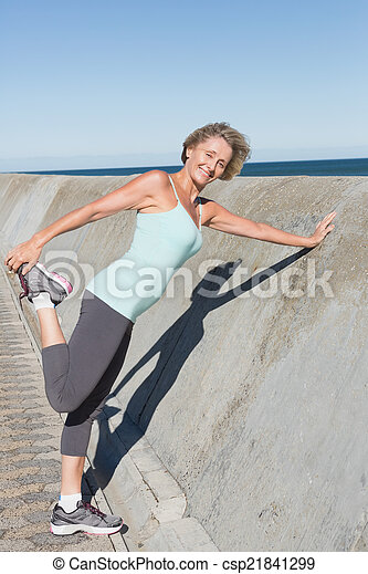 Active senior woman stretching on the pier - csp21841299