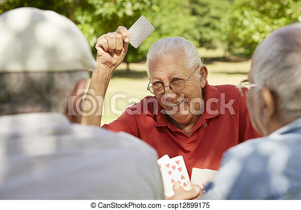 Active seniors, group of old friends playing cards at park - csp12899175