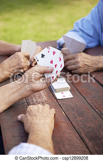 Active seniors, group of old friends playing cards at park - csp12899208