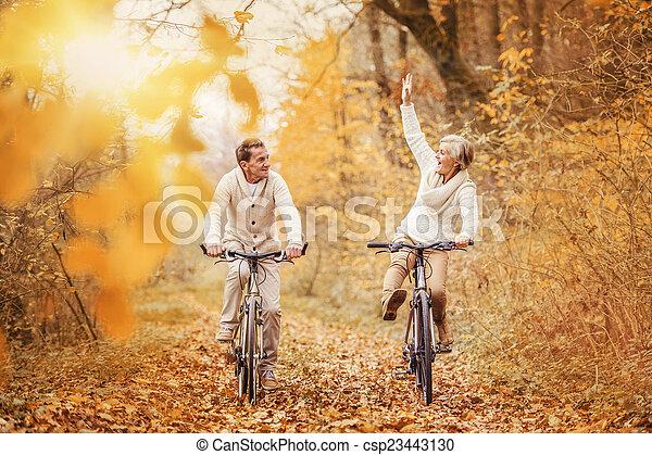 Active seniors ridding bike and having fun - csp23443130