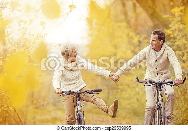 Active seniors riding bike - csp23539995