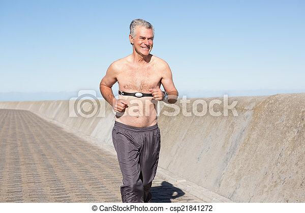 Active shirtless senior man jogging on the pier - csp21841272
