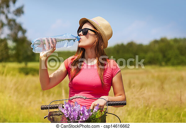 Active woman with bike drinking cold water - csp14616662