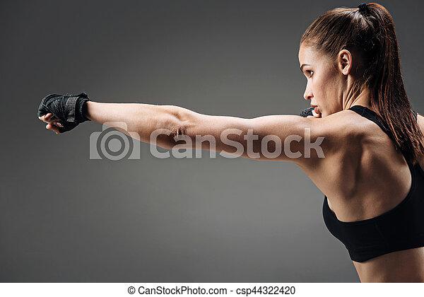 Una chica activa boxeando en un fondo gris - csp44322420