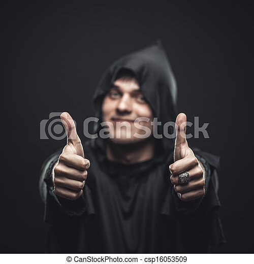 Un tipo con una bata negra mostrando pulgares arriba - csp16053509