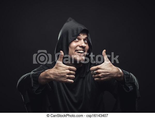 Un tipo con una bata negra mostrando pulgares hacia arriba - csp16143407