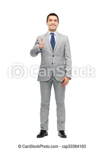 Un feliz hombre de negocios con traje mostrando pulgares arriba - csp33364163