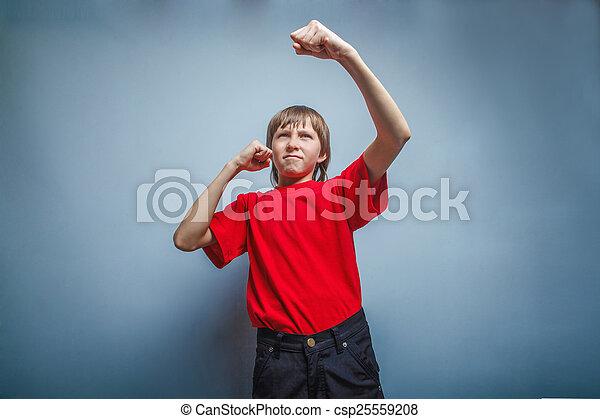 Chico, adolescente, doce años con camisa roja, mostrando sus puños - csp25559208