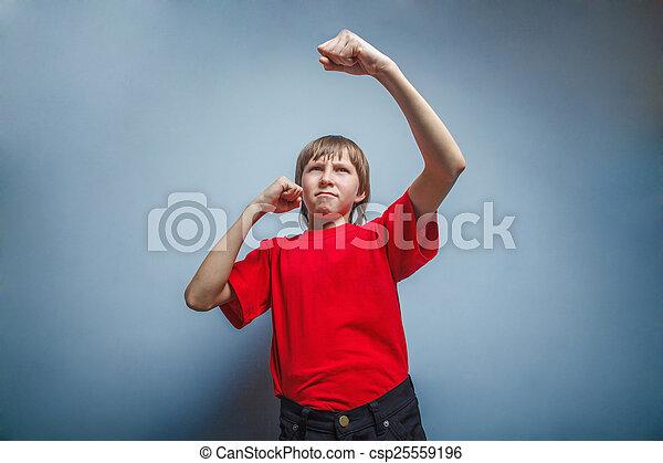 Chico, adolescente, doce años de camisa roja, mostrando sus puños - csp25559196