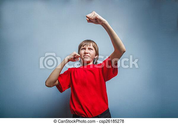 Chico, adolescente, doce años con una camisa roja, mostrando sus puños - csp26185278