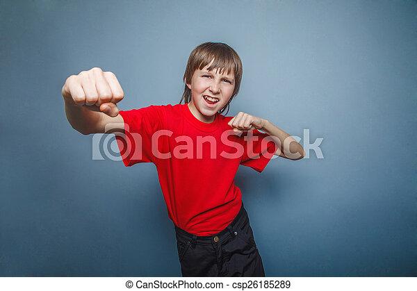 Chico, adolescente, doce años con su camisa roja, mostrando los puños - csp26185289