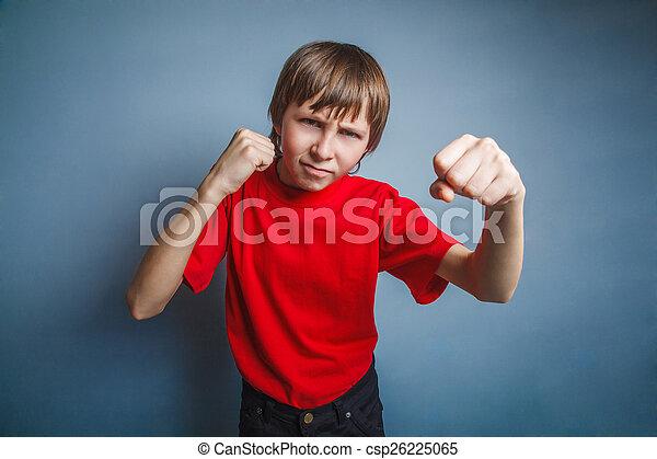 Chico, adolescente, doce años con una camisa roja, mostrando sus puños, - csp26225065