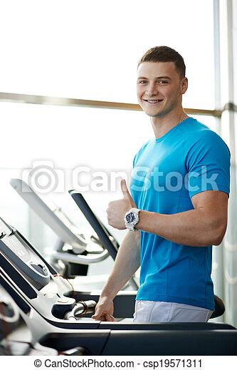 Hombre mostrando pulgares cerca de la cinta de correr - csp19571311