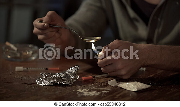 Addict heating heroin dose in spoon with lighter, injectors and white lie around - csp55346812