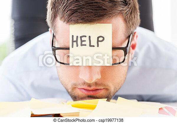 Necesita ayuda. Un joven frustrado con ropa formal con una nota adhesiva en la frente apoyando su cabeza en la mesa - csp19977138