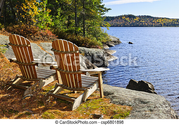 Adirondack chairs at lake shore - csp6801898