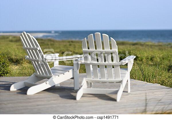 Adirondack chairs on deck looking towards beach on Bald Head Island, North Carolina. - csp1491771