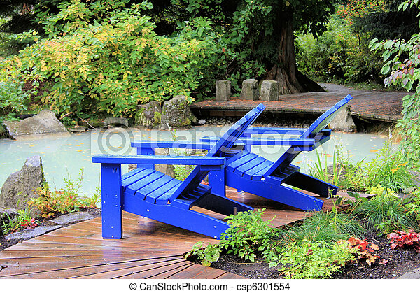 Two Bright Blue Adirondack Chairs On The Edge Of A Pond