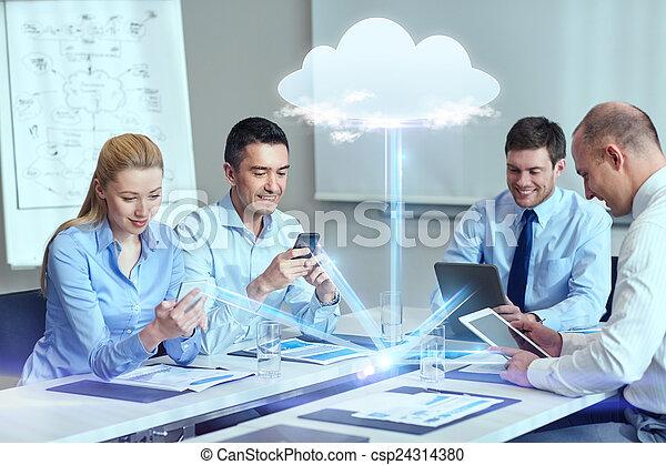 Gente sonriente de negocios con aparatos en la oficina - csp24314380