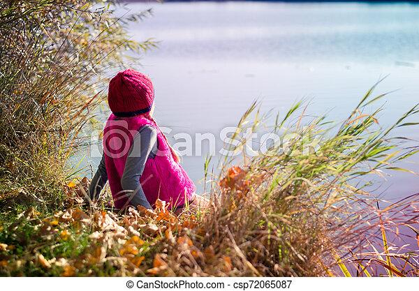 admiring water in autumnal sunset atmosphere - csp72065087