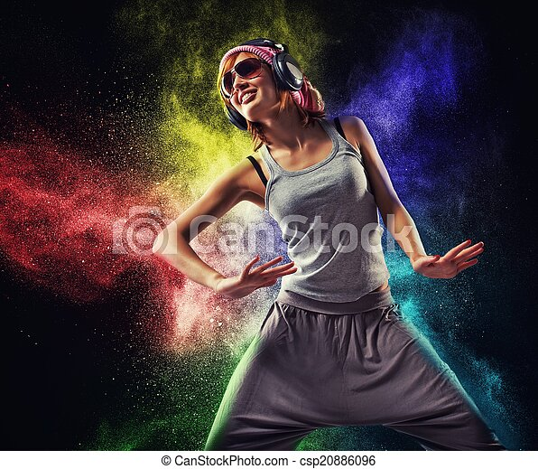 Una adolescente con audífonos bailando contra una explosión de pólvora - csp20886096