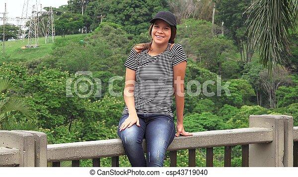 Una adolescente sonriente sentada - csp43719040