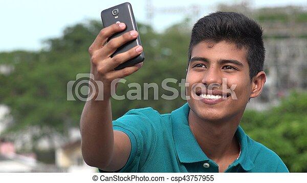 Un apuesto adolescente tomando autoestima y sonriendo - csp43757955