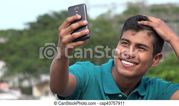 Un apuesto adolescente tomando autoestima y sonriendo - csp43757911