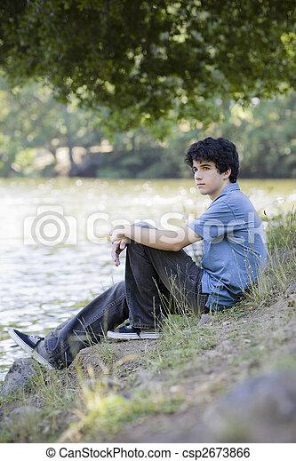 Un adolescente sentado junto al lago - csp2673866