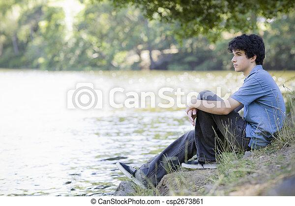 Un adolescente sentado junto al lago - csp2673861