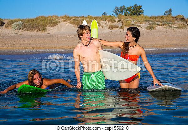 Felices surfistas adolescentes hablando en la playa - csp15592101