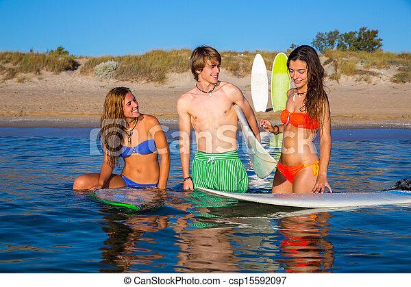 Los surfistas felices hablando en la playa - csp15592097