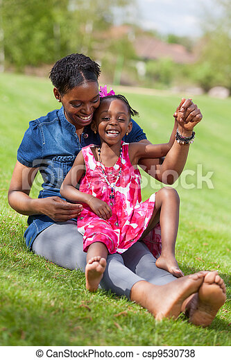 Adorable african mother with her daughter in the garden - csp9530738