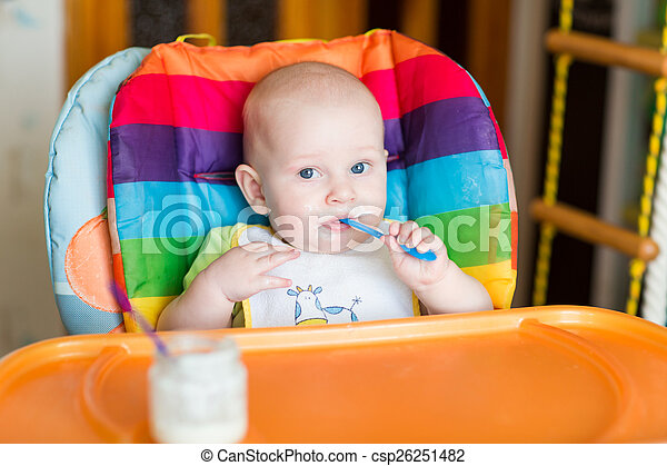 Adorable baby eating in high chair - csp26251482