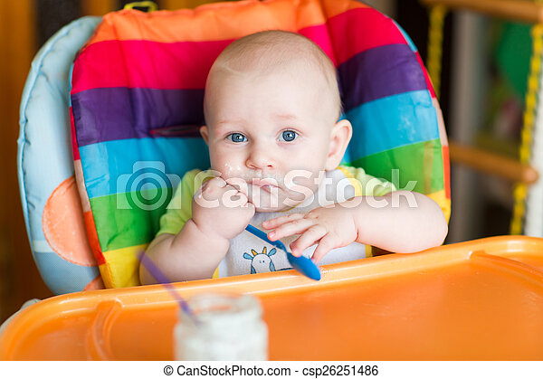 Adorable baby eating in high chair - csp26251486