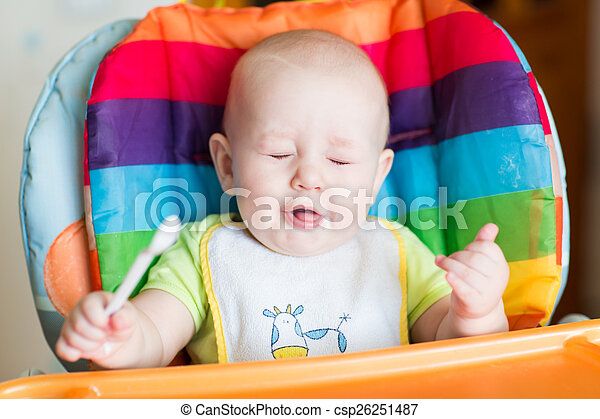 Adorable baby eating in high chair - csp26251487